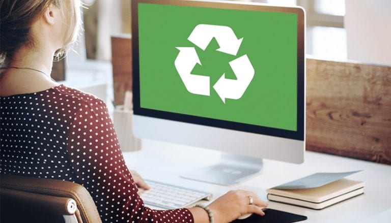 woman on computer with green recycling diagram on her computer