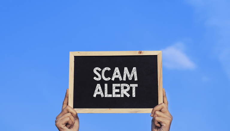 gentleman holding Scam Alert sign up