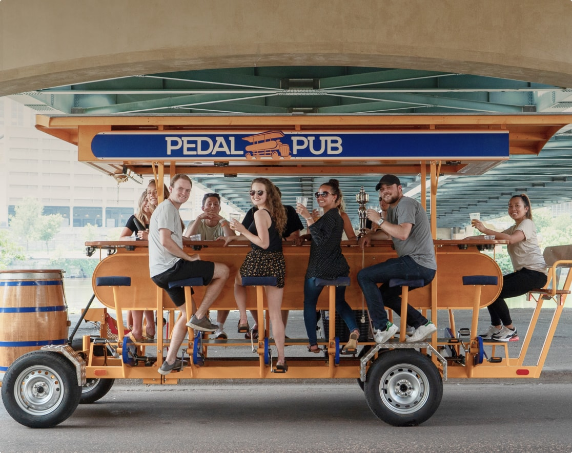 group of friends sitting on the pedal pub bike cheering